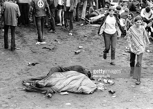 At the Kickapoo Creek Rock Festival concert goers walk past two people in sleeping bags on the ground near Heyworth Illinois 1970