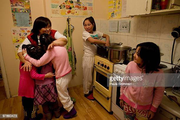 At the Lighthouse girls shelter Mongolian girls get a hug from the caretaker while dinner is prepared in the kitchen March 10 2010 in Ulaan Baatar...