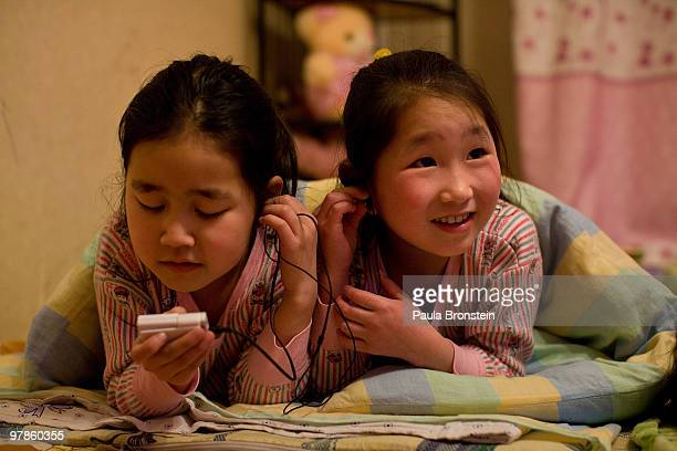 At the Lighthouse girls shelter Mongolian girls share headphones as they get ready for bed March 10 2010 in Ulaan Baatar Mongolia The police picked...