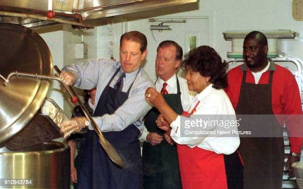At the Martha's Table volunteer center US Vice President Al Gore pours vegetable ingredients into a commercial soup pot as from second left US...