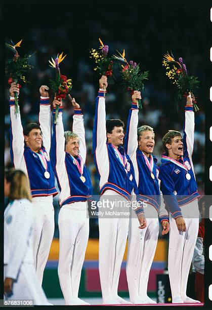 At the medals ceremony following their victory in men's team gymnastics competition, members of the American team wear their gold medals and wave...