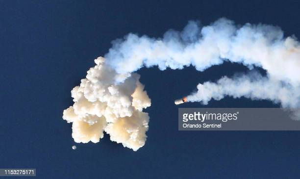 At the moment of the abort manuever, the Orion test capsule can be seen emerging from the separation cloud, with the Minotaur 4 booster falling ,...