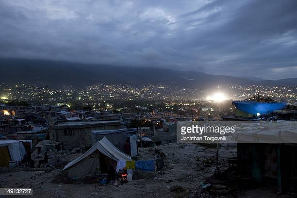 At the neighborhood of Fort National residents watch TV on top of a building that was damaged during the earthquake in a makeshift tent February 2011...