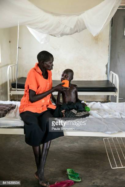 At the Nyumanzi health clinic a mother feeds her severely malnourished child The Onward Struggle A refugee crisis in Uganda deepens as South Sudanese...