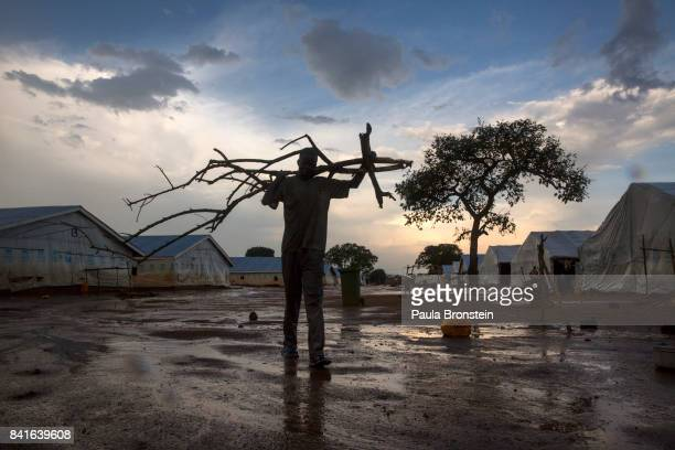 At the Nyumanzi transit camp a man carries firewood The Onward Struggle A refugee crisis in Uganda deepens as South Sudanese Refugees are forced to...