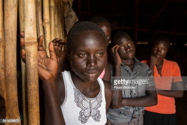 At the Nyumanzi transit camp Esther Ababiku stands with other young Sudanese women who are orphans of the war after loosing their parents they were...