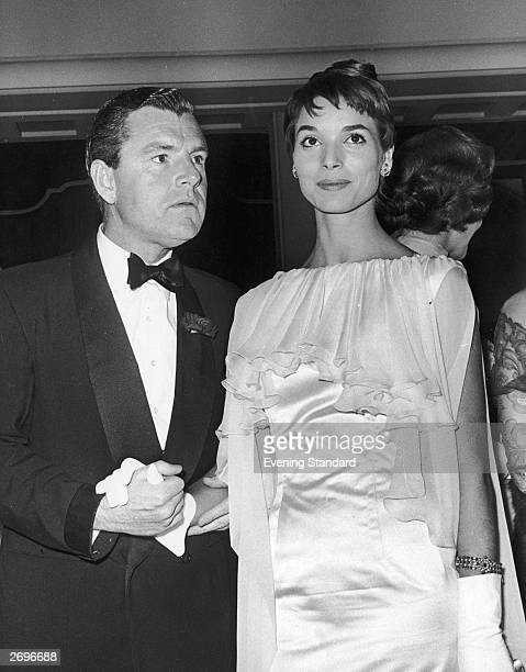 At the Odeon Cinema Marble Arch London film star Kenneth Moore holds hands with Italian actress Elsa Martinelli who is wearing an evening dress with...