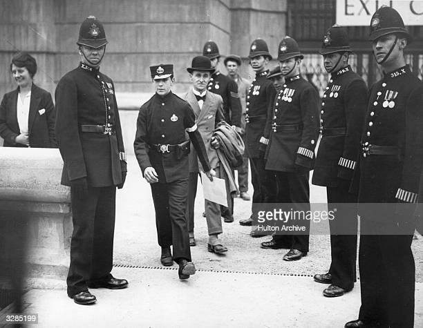 At the opening of the British Empire Exhibition at Wembley Henry Annals flanked by police takes the King's message to the Empire after it had been...