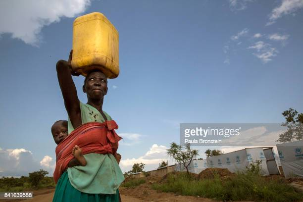 At the Pagarinya camp a mother carries water back to her tent The Onward Struggle A refugee crisis in Uganda deepens as South Sudanese Refugees are...