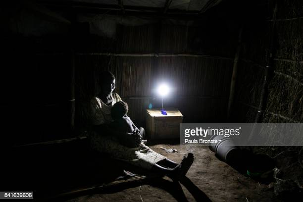 At the Pagarinya camp a mother holds her baby with a dim solar lamp which is the only light source given to the refugees The Onward Struggle A...