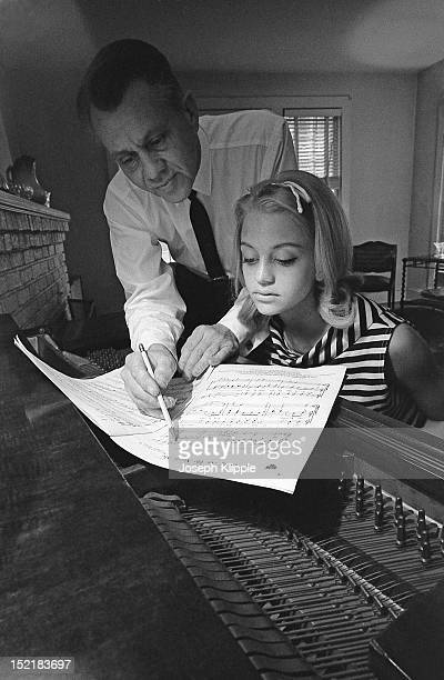 At the piano with her father musician and bandleader Edward Rutledge Hawn American teenager and future dancer and actress Goldie Hawn looks over...