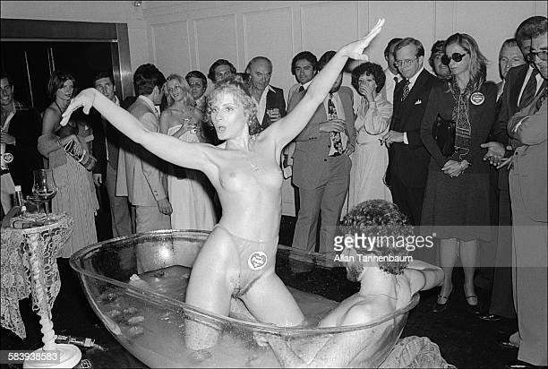 At the Purple magazine party a mostly naked couple in a clear bathtub perform for men and women in business attire New York New York September 15...