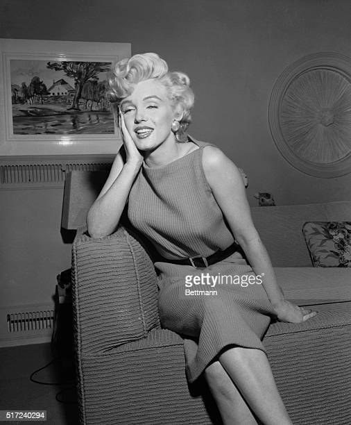 At the request of curious newsmen Marilyn Monroe removes the belt of her tight orange knot dress as she returns to work at Twentieth Century Fox...