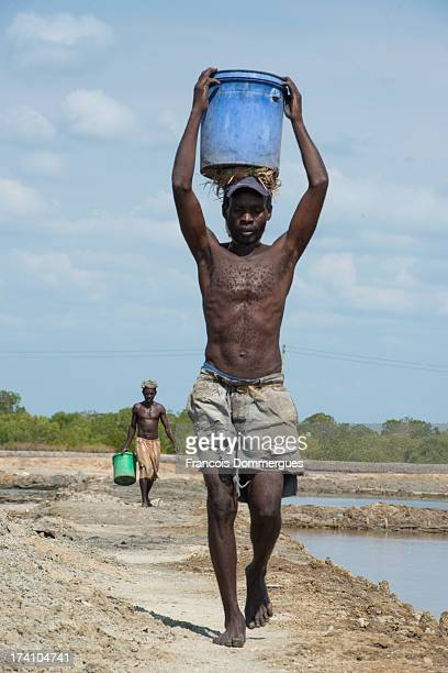 At the salt marshes of Kilwa Masoko, workers carry large buckets of salt on their heads. The way they walk in line is amusingly similar to a fashion...