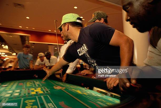 At the Southern Belle Casino a gambler tosses the dice on the craps table as others watch