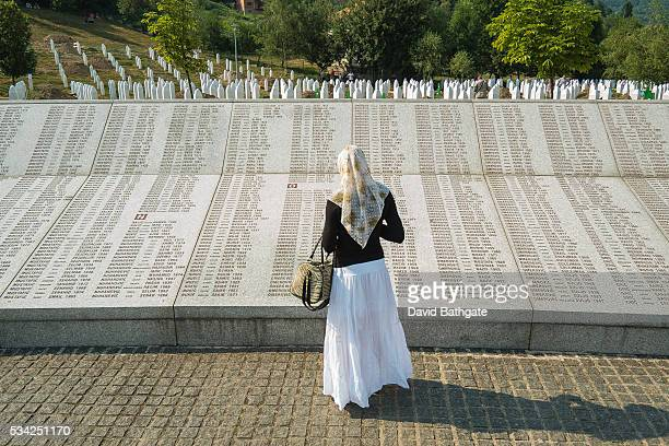 At the SrebrenicaPotocari Memorial and Cemetery a Muslim woman reads names of victims of the July 1995 Srebrenica massacre carried out by Bosnian...