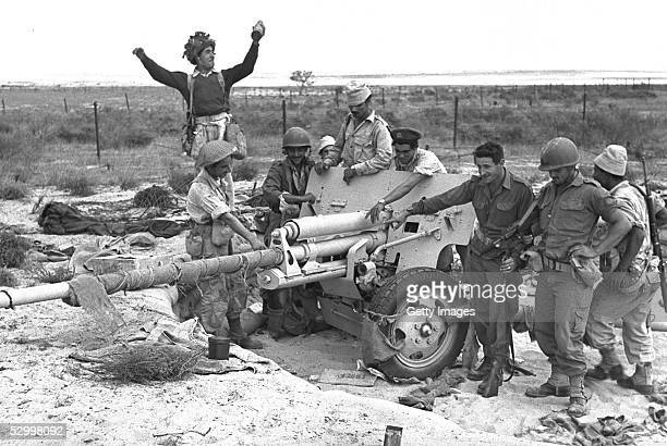 At the start of Israel's first occupation of this wartorn area invading Israeli infantry troops celebrate the capture of an artillery piece during...