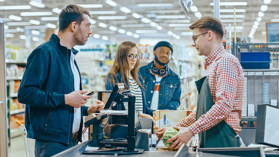 At the Supermarket: Checkout Counter Customer Pays with Smartphone for His Items. Big Shopping Mall with Friendly Cashier, Small Lines and Modern Wireless Paying Terminal System. 1087249406