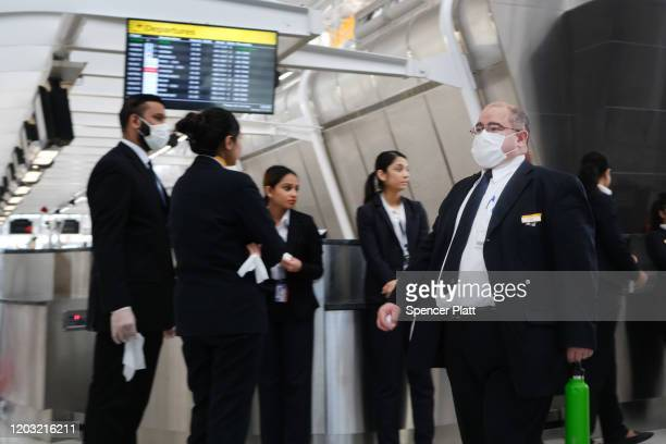 At the terminal that serves planes bound for China airport employees wear medical masks at John F Kennedy Airport out of concern over the Coronavirus...