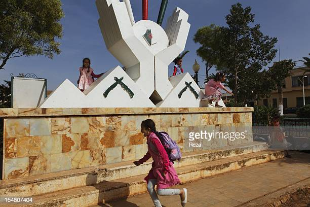 At the town hall square school children play on April 14 in El Malah Algeria around monuments dedicated to the martyrs who died during the Algerian...