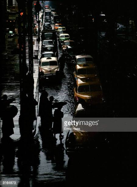 At the traffic lights pedestrians are crossing a street full of cars and yellow cabs on a dark wet day in New York