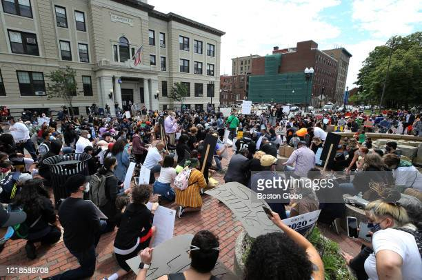 At the urging of Lawrence Mayor Daniel Rivera with megaphone at center right protesters kneel for 8 minutes and 46 seconds during a protest at...