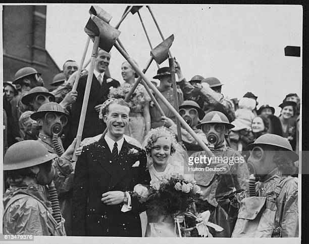 At the wedding of Dorothy Laura Tracher and Mr W G Clements the guard of honour wear gas masks and helmets and carry incendiary bomb scoops with...