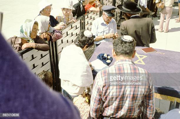 At the Western Wall in Jerusalem, Israel, several women wearing hats and shawls peer over the divider between the male and female sections of the...