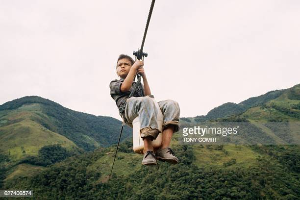 At Vilavivencio 200 kilometers from Bogota there are no roads through the valley Children use cables as a sort of trolley to and from school or to...