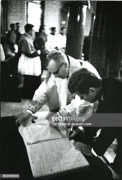 At Westminster Cathedral English priest Gordon Wheeler watches as US President John F Kennedy signs the registry London England June 5 1961 Kennedy...