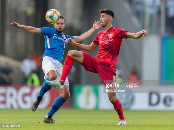 Atakan Karazor of VfB Stuttgart is challenged by Pascal Breier of Hansa Rostock during the DFB Cup first round match between Hansa Rostock and VfB...