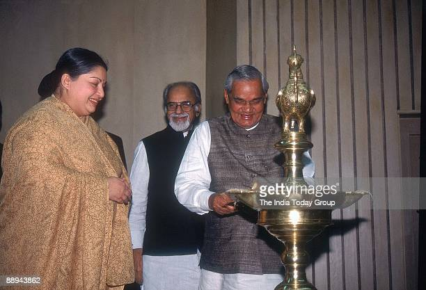 Atal Bihari Vajpayee lighting the lamp J Jayalalitha and Inder Kumar Gujral watching at a seminar on democracy in New Delhi