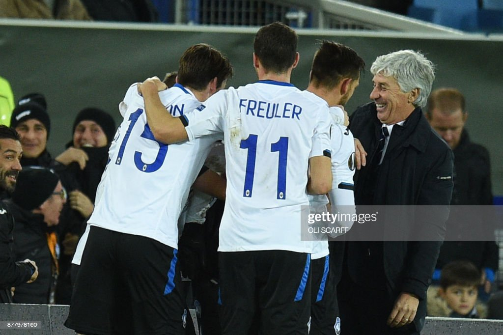 Atalanta manager Gian Piero Gasperini (R) celebrates the third goal with players during the UEFA Europa League Group E football match between Everton and Atalanta at Goodison Park in Liverpool, north west England on November 23, 2017. / AFP PHOTO / Oli SCARFF