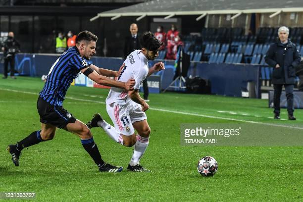 Atalanta's Albanian defender Berat Djimsiti holds back Real Madrid's Spanish midfielder Marco Asensio during the UEFA Champions League round of 16...