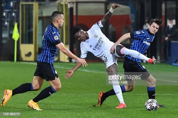 Atalanta's Brazilian defender Rafael Toloi, Real Madrid's Brazilian forward Vinicius Junior and Atalanta's Dutch midfielder Marten de Roon go for the...
