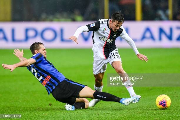 Atalanta's Brazilian defender Rafael Toloi tackles Juventus' Argentine forward Paulo Dybala during the Italian Serie A football match Atalanta...