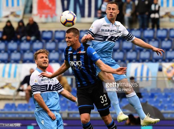 Atalanta's Dutch defender Hans Hateboer vies for the ball with Lazio's midfielder from Montenegro Adam Marusic and Lazio's Italian forward Ciro...