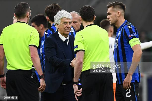 Atalanta's Italian head coach Gian Piero Gasperini shakes hand with the referees at the end of the UEFA Champions League round of 16 first leg...