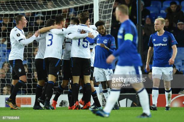 Atalanta's Italian midfielder Bryan Cristante celebrates with teammates scoring the team's first goal as England's striker Wayne Rooney looks on...
