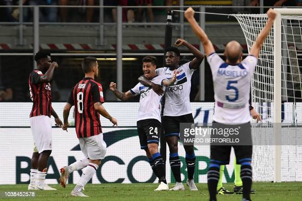 Atalanta's Italian midfielder Emiliano Rigoni celebrates with a teammate after scoring during the Italian Serie A football match AC Milan vs Atalanta...