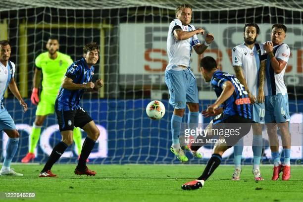 Atalanta's Ukrainian midfielder Ruslan Malinovskyi shoots a free kick as Lazio's Italian forward Ciro Immobile jumps to counter the ball during the...