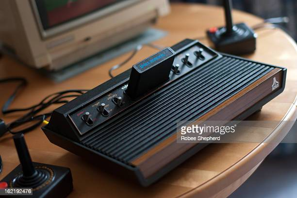 Atari 2600 VCS console, full view, with joysticks and Commodore 1084S monitor partially visible. 1978 six switch model. Space Invaders game is...