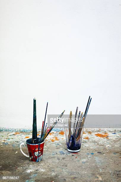 Atelier floor with used brushes in glasses