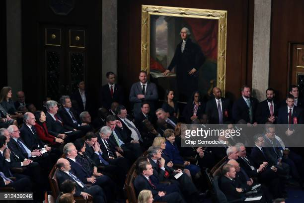 Atendess watch as US President Donald J Trump delivers the State of the Union address in the chamber of the US House of Representatives January 30...