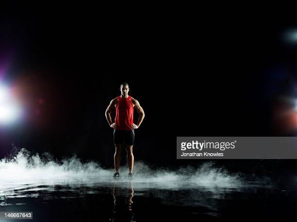 athelete standing in water at night - dry ice stock pictures, royalty-free photos & images