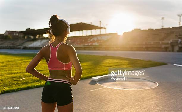 Athelete with headphones standing in stadium, rear view