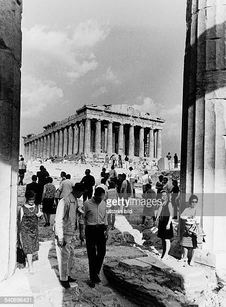 Athen, Griechenland: Akropolis. Besucher wandeln zwischen Säulen und über Marmorplatten; im Hintergrund ist der Säulenbau des Parthenon zu sehen....