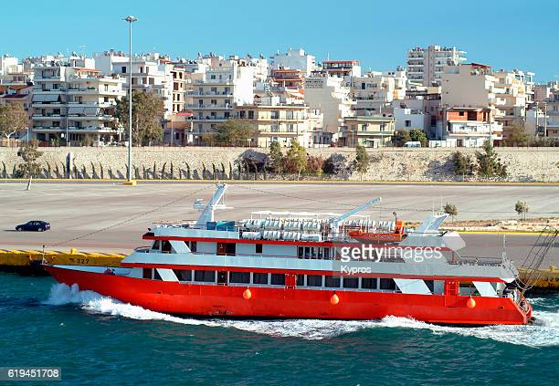 athens europe, piraeus port, greece, view of red boat with apartment buildings in background - piraeus stock photos and pictures