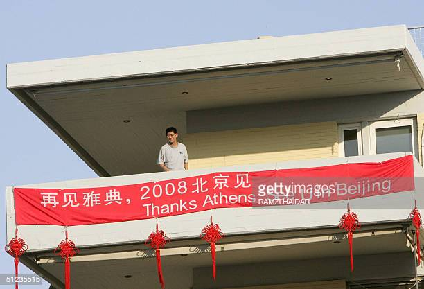 Chinese man stands on a balcony with a banner hanging from it that refers to the upcoming '2008 Olympic Games in Beijing', on the last day of the...