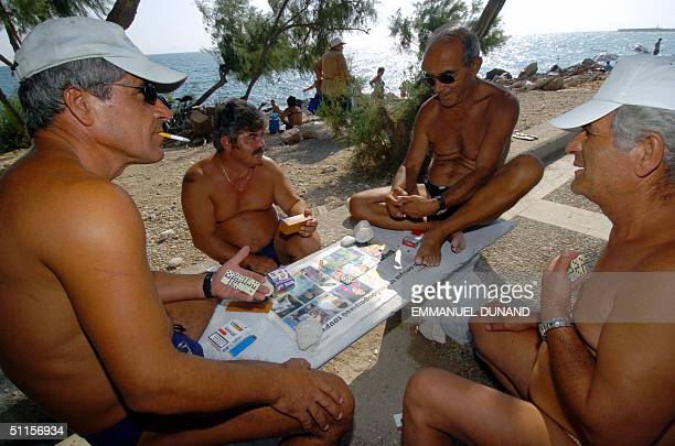 A group of Greek men enjoy a seaside game of dominoes near the Helliniko Olympic sports complex 10 August 2004 three days before the beginning of the...